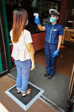 Each customer undergoes a mandatory temperature check and passes through a foot bath disinfection mat as they enter the store.